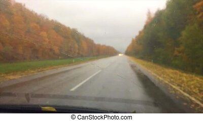 cars go on the road asphalt. autumn travel beautiful view forest, raindrops on the glass car blurred background slow motion video