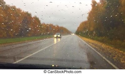 cars go on the road asphalt. autumn travel beautiful view forest, raindrops on the glass car blurred background slow motion video drive