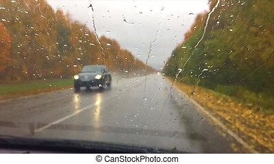 cars go on the road asphalt. autumn travel beautiful view forest, raindrops on the glass car drive blurred background slow motion video