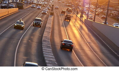 Cars go on the road in the evening light of sunset
