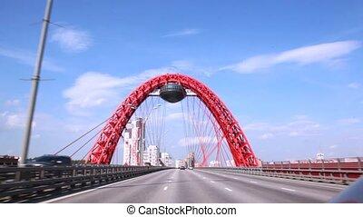 Cars go on Zhivopisny Bridge against blue cloudy sky