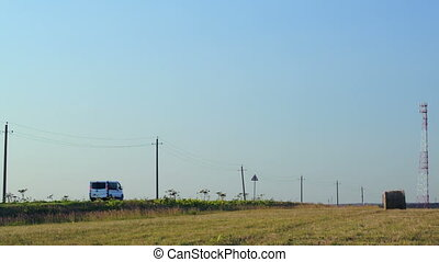 Cars going by field with hay roll in countryside