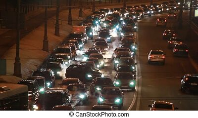 cars in hard traffic jam on wintry street of city