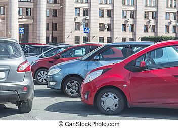 Cars in parking place near classic style building. - Cars in...
