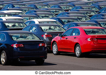 A lot of new cars stored in an industrial yard, waiting for transport.