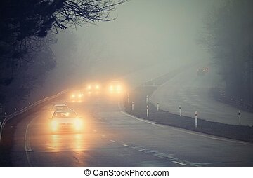 Cars in the fog. Bad winter weather and dangerous automobile traffic on the road. Light vehicles in fog.