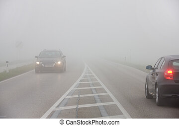 Cars in the fog on a road - Cars driving in the fog on a...