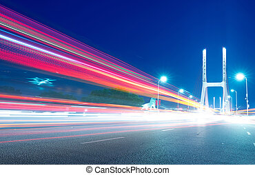 cars light trails on the modern bridge at dusk