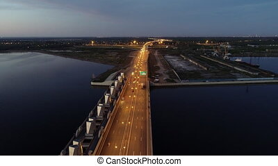 Cars moving on highway bridge on the sea directing to the industrial