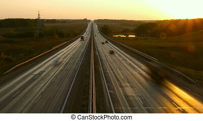 cars on highway road at sunset, zoom in timelapse
