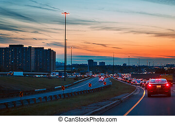 cars on highway road on sunset evening night in busy city -...