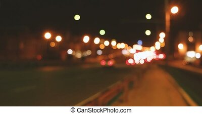 Cars on overpass in nighttime defocused footage. - Cars move...