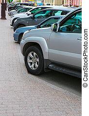 cars on parking near sidewalk in row in city