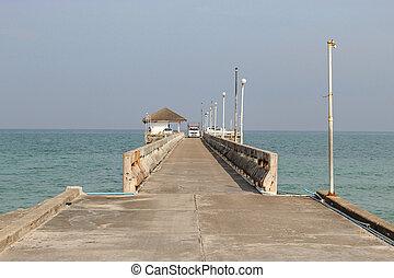 Cars on the concrete bridge pier fishing in the sea.