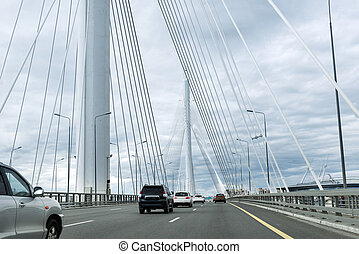 cars on the road on the bridge with metal cables, arch of the bridge