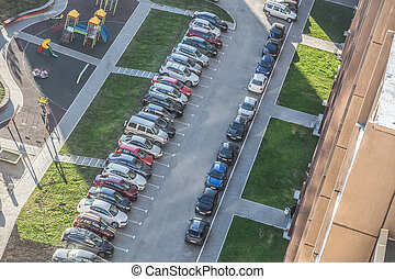 Cars parked in the courtyard of a residential apartment building.