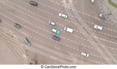 Cars pass a multi-lane complex intersection with traffic lights - drone drone tilt and pan shot. City traffic at the intersection of a large multi-lane highway.