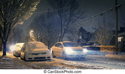 Cars drive past residential area in evening in heavy snowfall