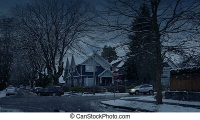Cars Pass Houses In Snowfall In The Evening