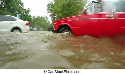 Cars passing a flooded intersection - cars slowly moving at...
