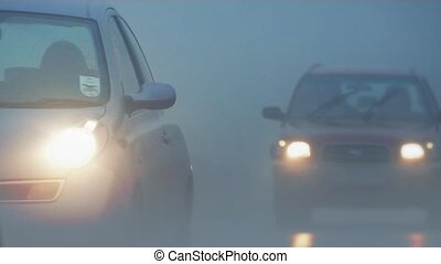 Many cars drive past in heavy fog
