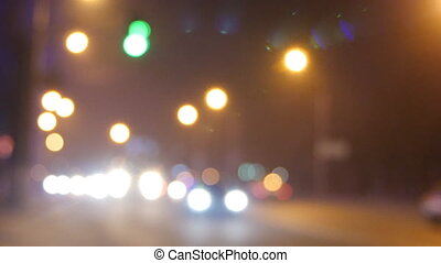 Cars passing on red traffic light signal. Out of focus background with blurry unfocused city lights and driving cars and car light