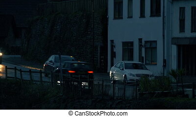 Cars Passing Through Village In The Evening
