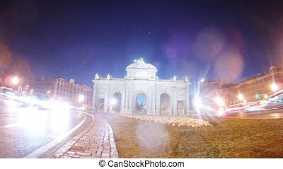 Cars quickly go on road near Puerta de Alcala, time lapse