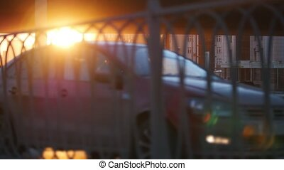Cars riding on the road on a sunset. A view through unfocused fence in a foreground