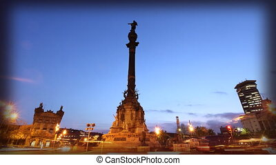 cars rushing by at night past the famous colon statue,...