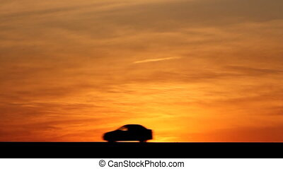 Cars silhouettes on road against sunset