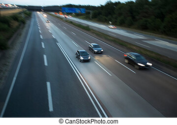 cars speeding on a highway in the evening