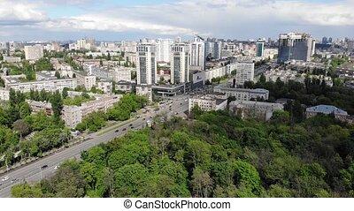 Cars traffic skyscrapers aerial clouds blue sky cityscape multistory houses apartment Kyiv Ukraine backward movement tilt up