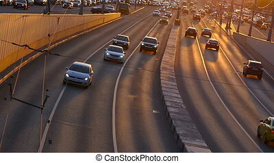 Cars traveling in the light of the sunset