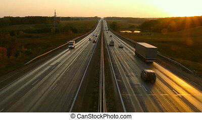 cars traveling on the highway road at sunset