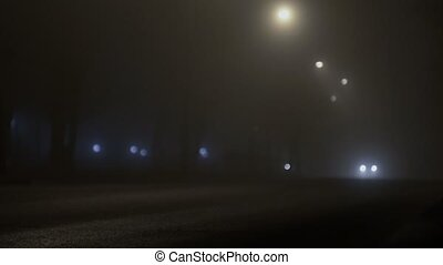 cars with headlamps driving on a road in the mist at night,...
