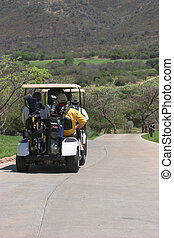 Cart - Golfers driving off in golf cart after teeing off