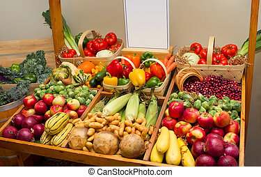 large harvest of fruits and vegetables with a blank sign