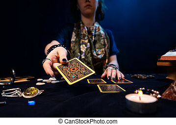 Cartomancy. Fortune-telling on cards. The fortune teller hands over a Tarot card. The concept of divination, astrology and esotericism