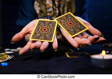 Cartomancy. The fortune teller holds out two Tarot cards on her palms. Close up. The concept of divination, astrology and esotericism