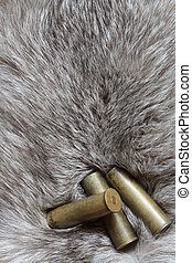 Three cartridges lying on background with nice gray silver fox fur
