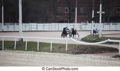 carts of running horses with jockeys come