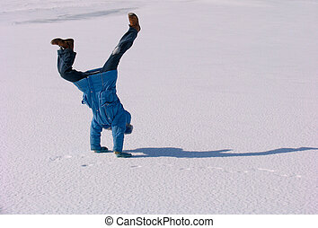 Cartwheel on the snow - Young girl making Cartwheel on the...