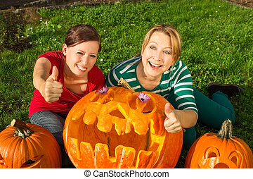 Carve a pumpkin - Two girlfriends with a big Halloween...