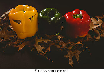Carved bell peppers with autumn leaves over black background