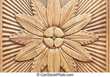 Carved flower on wooden background
