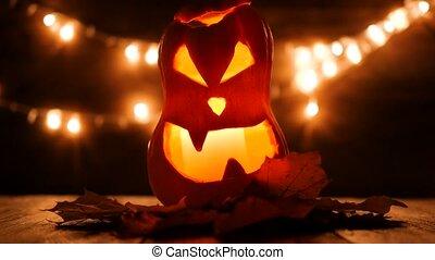 Carved Halloween pumpkin with lights on background. Dark key...