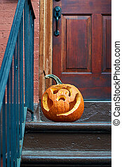 Carved Halloween pumpkins or jack o'lantern on the doorstep in Brooklyn