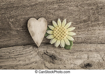 heart and daisy flower on wooden background