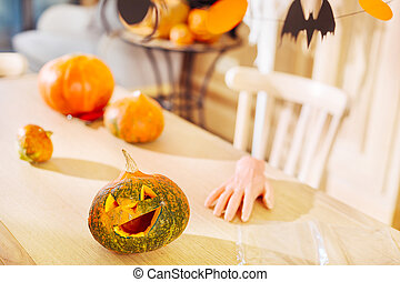 Close up of carved Halloween pumpkin lying on the table near witches fingers cookie